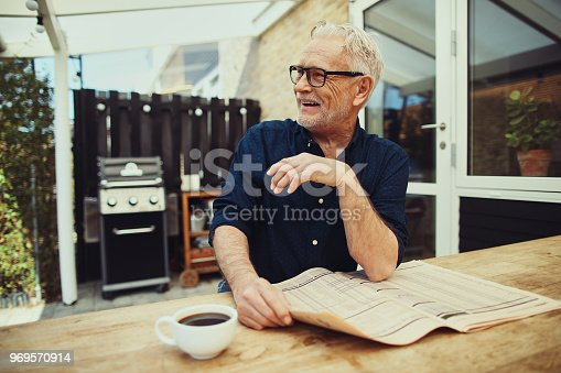 116379055 istock photo Content senior man sitting at his patio table laughing 969570914