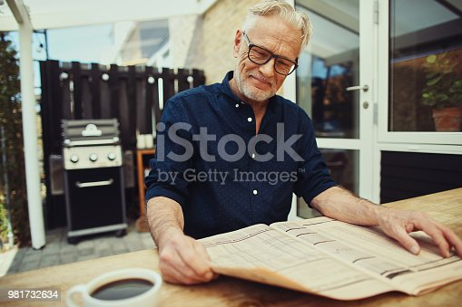 116379055 istock photo Content senior man sitting on his patio reading a newspaper 981732634