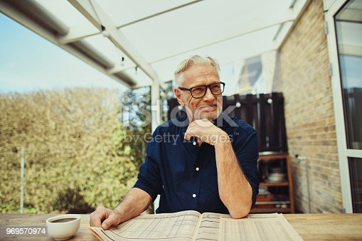116379055 istock photo Content senior man sitting on his patio reading the newspaper 969570974