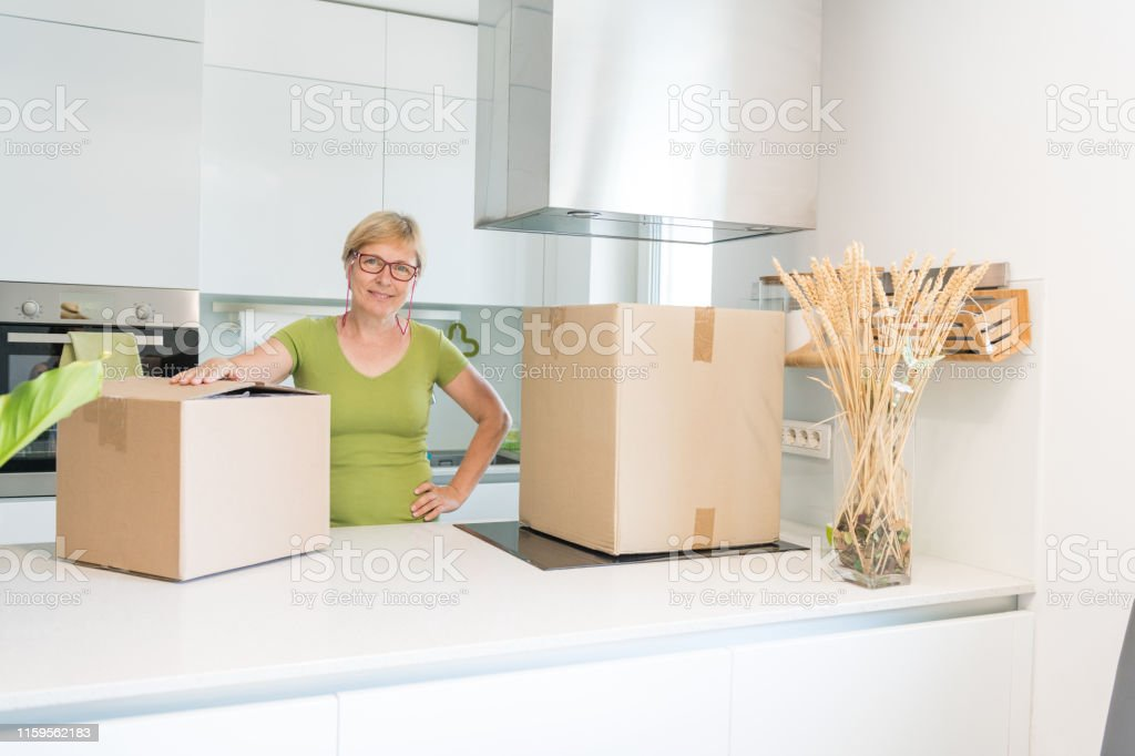 Content Senior Woman between packaging boxes