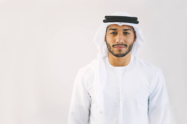 Content Young Arab Man in Traditional Clothing Young and confident Emirati man is standing in front of light grey wall, hands let down, looking at the camera smiling lightly. Model's clothing is white and black making good contrast with his face. Image contains copy space on the left. Made in Dubai, United Arab Emirates. arabic style stock pictures, royalty-free photos & images