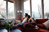 Content young couple sitting together on their living room sofa and looking out through windows at the rain