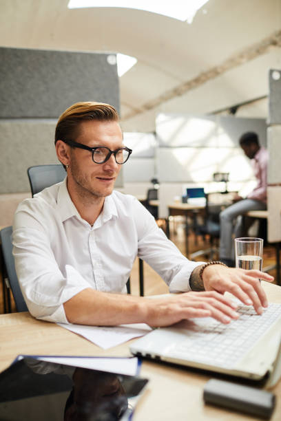 Content young man in eyeglasses sitting at desk and typing on laptop while working on article for social media stock photo