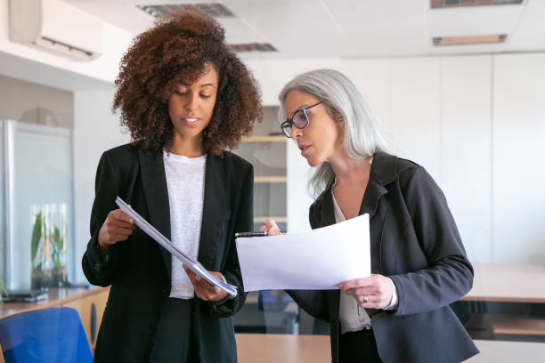 Content young manager showing document to adult colleague stock photo
