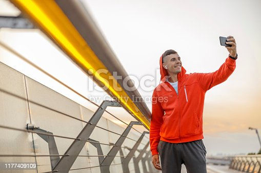 Smiling young Caucasian man taking selfies on a pedestrian bridge in the morning