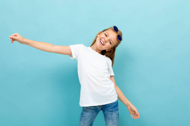 contented charismatic girl schoolgirl in a white t-shirt on a blue background stock photo