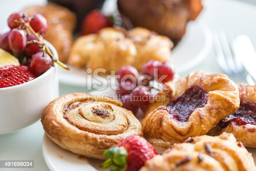 Closeup of a continental breakfast at a hotel, with bowls and plates filled with a selection of breakfast bakery items and fresh fruit on a white table with cutlery in the background.