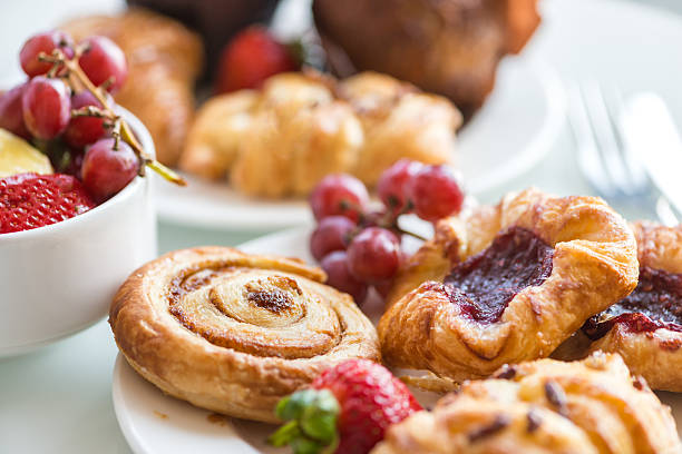 continental breakfast - cinnamon bun, danishes, rolls, muffins, fresh fruit - ontbijt stockfoto's en -beelden