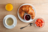 istock continental Breakfast - coffee, croissant with jam, strawberries and orange juice on wooden background 842266690