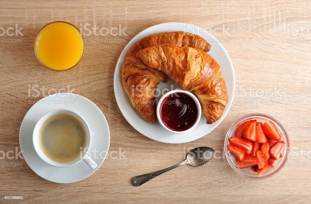 pequeno-almoço continental - café, croissant com geleia, morangos e suco de laranja em fundo de madeira - foto de acervo