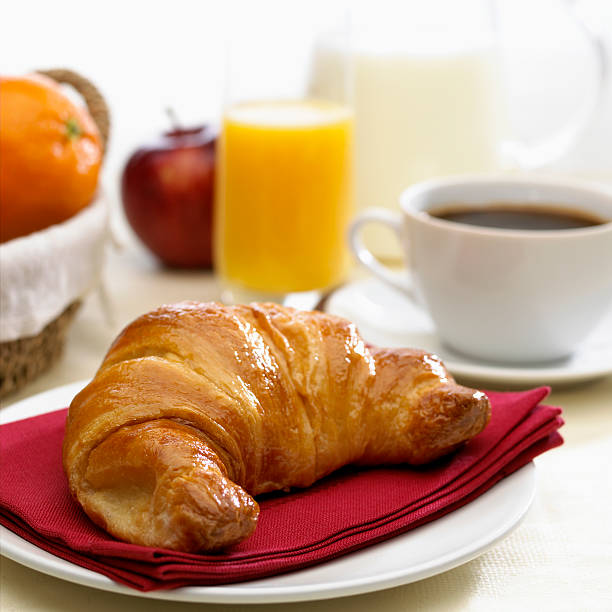 Continental breakfast coffee milk orange juice and croissant stock photo