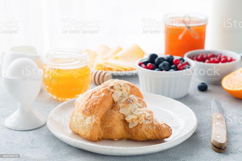 Kontinentales Frühstück Croissant, Honig, Marmelade, Beeren und Ei – Foto