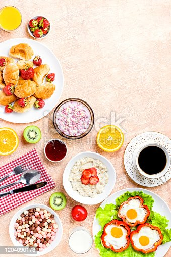 Continental breakfast with cereal, fried eggs, croissants, fruits and drinks on textured table