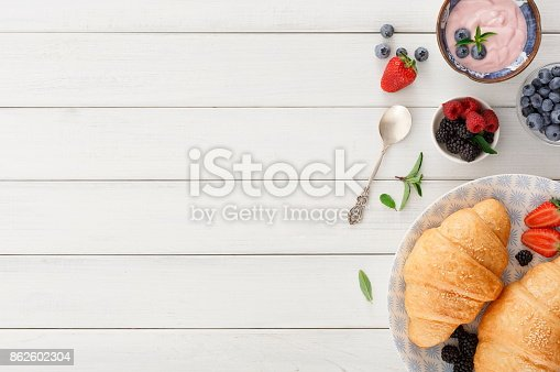 istock Continental breakfast with croissants and berries on checkered cloth 862602304