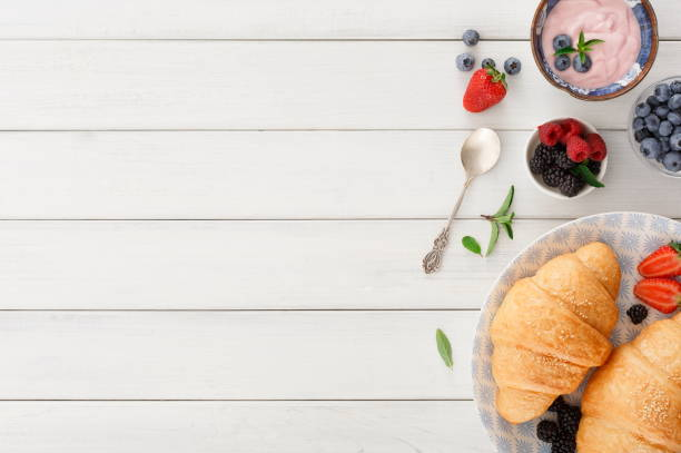 Continental breakfast with croissants and berries on checkered cloth stock photo