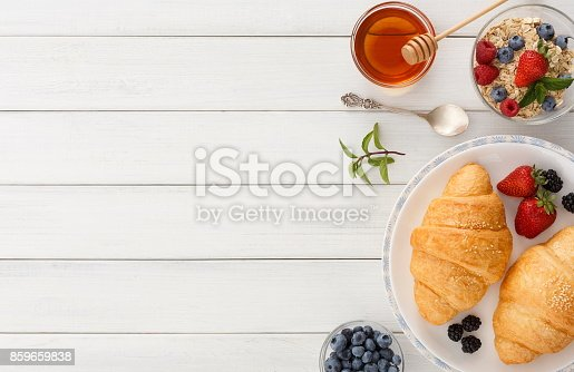 863562090istockphoto Continental breakfast with croissants and berries on white wood 859659838