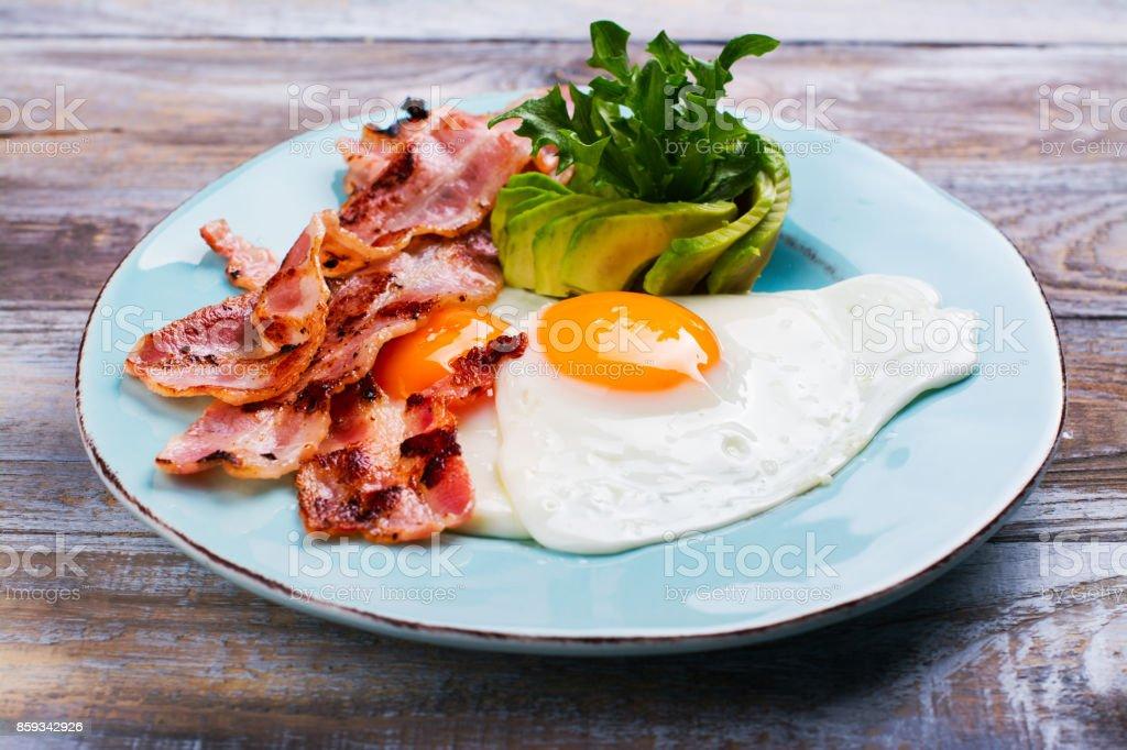 Continental breakfast with fried eggs, bacon and avokado stock photo