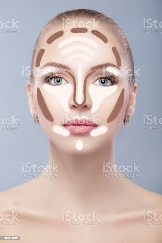 Contouring. Make up woman face on grey  background. Contour and highlight makeup. stock photo