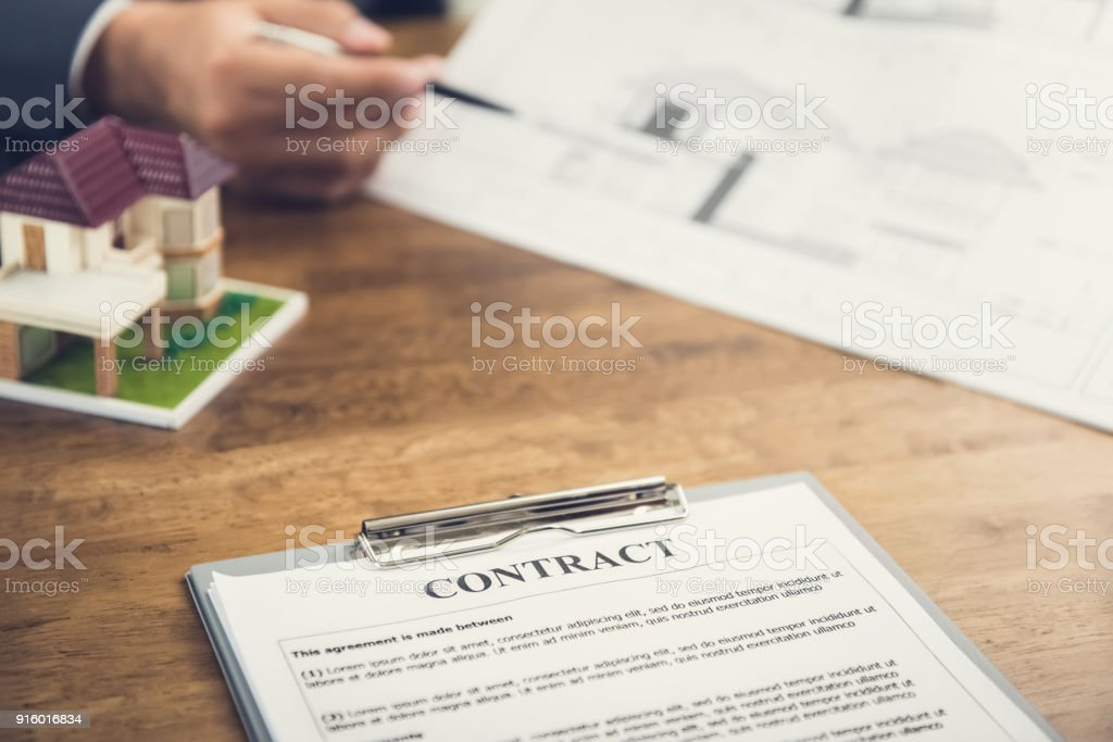 Contract agreement paper and house model on the table with blur hand contract agreement paper and house model on the table with blur hand of businessman reviewing blueprint malvernweather Image collections