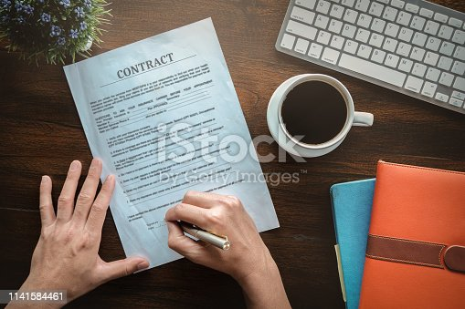 istock contract and agreement concept, man holding pen to sign contract application paper with coffee cup keyboard and notebook on wood desk in office bank. 1141584461