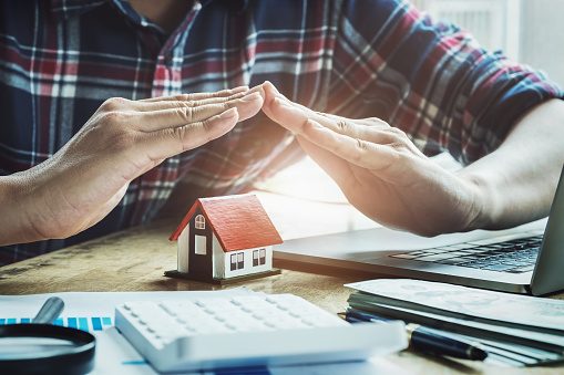 626187670 istock photo contract and agreement insurance contract concept, Insurance agent raises his hand hand protecting a house under his hands. 1170384158