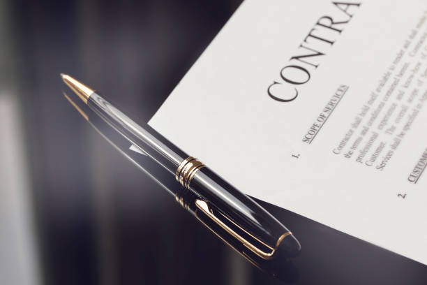 contract documents and fountain pen on black desk, business concepts stock photo