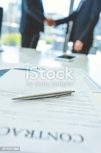 1072035844istockphoto Contract on a board room table with men shaking hands. 974341880