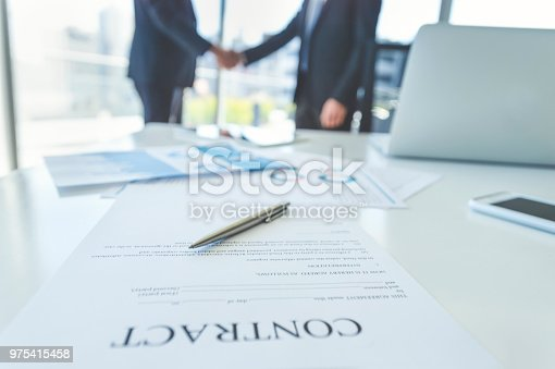istock Contract on a board room table with men shaking hands. 975415458