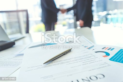 istock Contract on a board room table with men shaking hands. 975415460