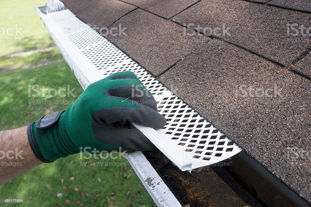 Contractor Adjusting Plastic Gutter Guards stock photo