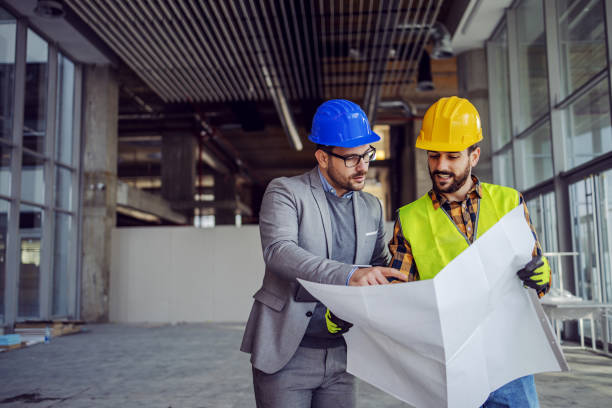 Contractor and architect looking at plan and talking about working on big project. Building in construction process interior. stock photo
