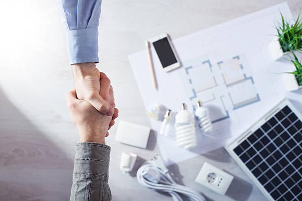 sous-traitant et client se serrant la main - efficacité énergétique photos et images de collection