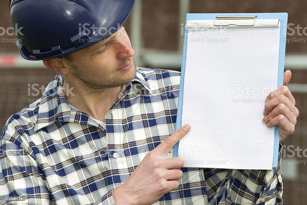 Contractor by construction holding piece of paper royalty-free stock photo