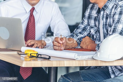 Contractor construction engineer meeting together on architect table at construction site. Business man and engineer manager discussing with foreman team builder blueprint planning design paperwork.