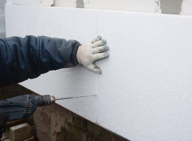 Aannemer boren muur voor piepschuim isolatie vellen houder. foto