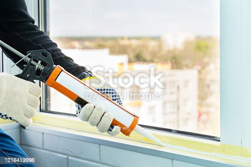 istock Contractor hand holding glue gun with silicone to repair tile and window. Installation or renovation interior concept. 1216419996