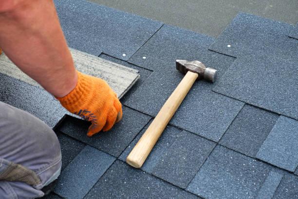 aannemer handen installeren bitumen dakshingles hamer met nagels. - dak stockfoto's en -beelden