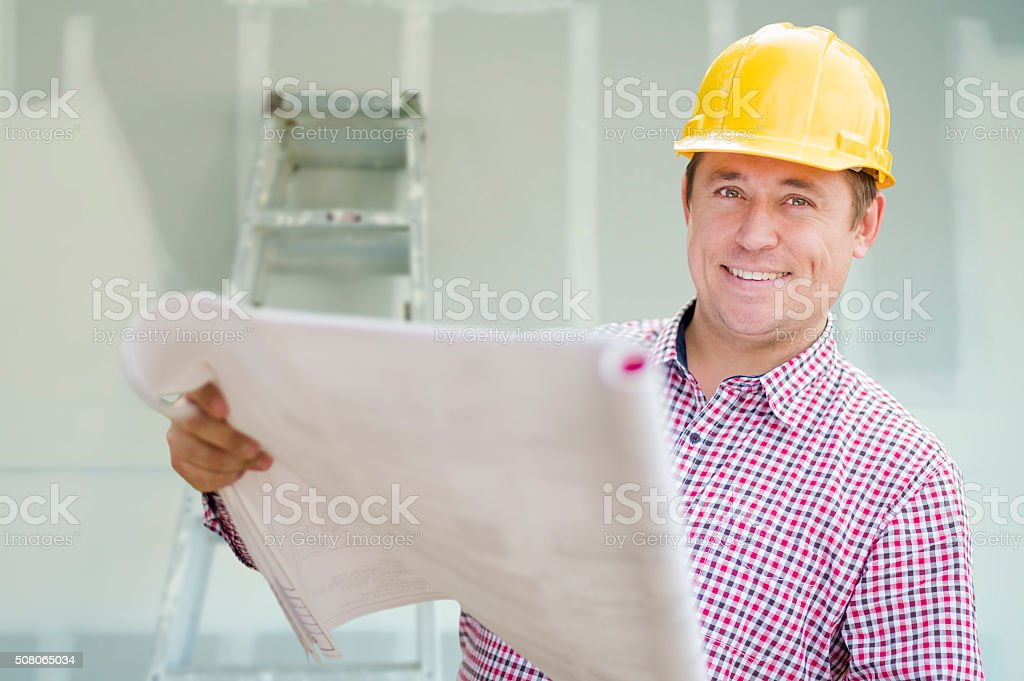 Contractor Holding Blueprints Inside Home Construction Site stock photo