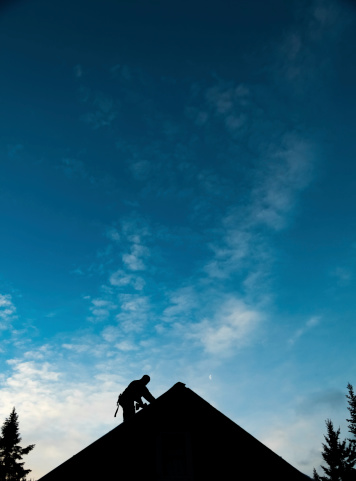 istock Contractor in Silhouette working on a Roof Top 504102095
