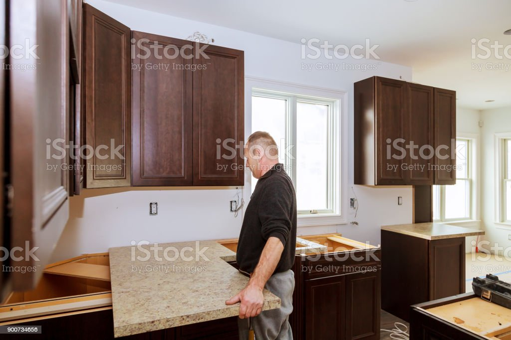 Contractor installing a new laminate kitchen counter top stock photo