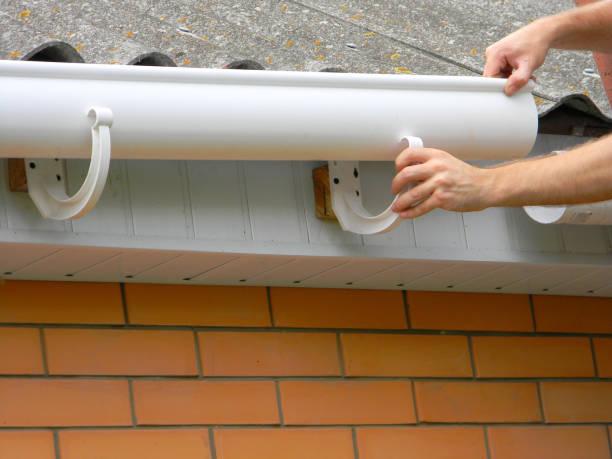Aannemer installeren van plastic dakgoten. Kunststof dakgoten vervangen, regengoot & drainage reparatie door Handy hands. foto