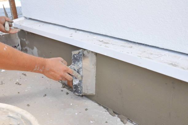 Een aannemer is pleisteren, repareren stucwerk huis stichting na piepschuim isolatie. foto
