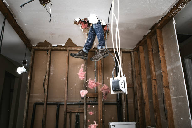 Contractor Man Doing Home Improvement and Demolition A man attempts to work on renovating his home, with funny and disastrous results.  He falls through the drywall ceiling feet first. negative emotion stock pictures, royalty-free photos & images