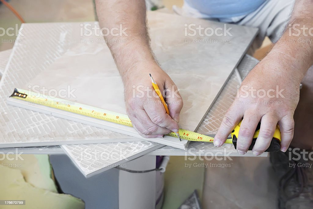 Contractor measuring tile royalty-free stock photo
