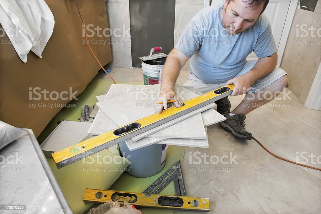 Contractor measuring tile to be put on bathroom wall royalty-free stock photo