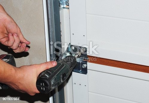 istock Contractor repair and replace garage door. Garage door installation. 901937664