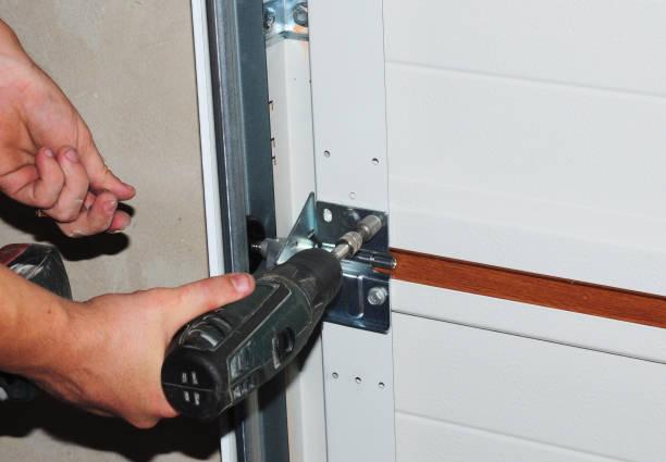 Aannemer repareren en vervangen van de garagedeur. De installatie van de deur van de garage. foto