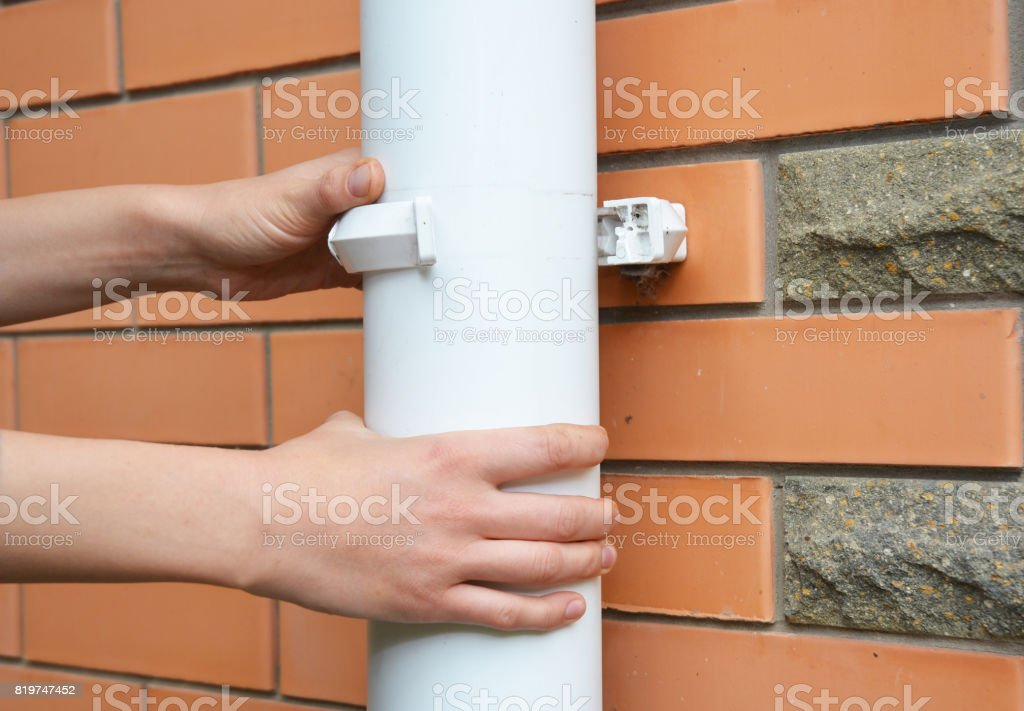 Contractor repair rain gutter downspout pipe. Roundline Guttering, Guttering & Drainage. stock photo