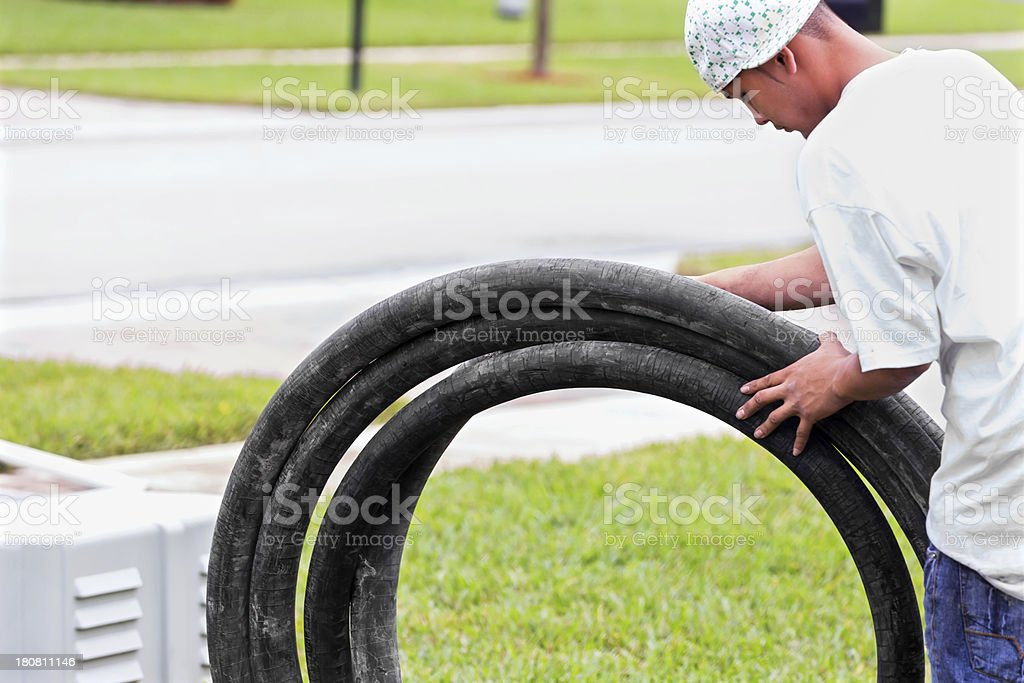 Contractor rolling a cement pumping hose stock photo