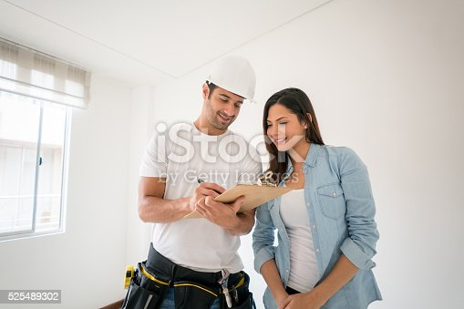 Latin American contractor talking to a woman at home about a housing project